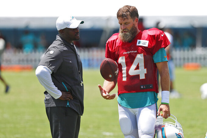 Miami Dolphins quarterback Ryan Fitzpatrick (14) talks with head coach Brian Flores after the teams NFL football training camp, Tuesday, July 30, 2019, in Davie, Fla. Flores says Fitzpatrick has become the front-runner in the Miami Dolphins' quarterback competition ahead of Josh Rosen. (AP Photo/Wilfredo Lee)