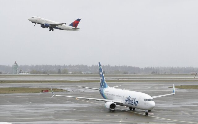 FILE - In this April 13, 2018 file photo, a Delta Air Lines plane takes off above a taxiing Alaska Airlines airplane at the Seattle-Tacoma International Airport in Seattle.  U.S. airlines are asking the federal government for grants, loans and tax relief that could easily top $50 billion to help them recover from a sharp downturn in travel due to the new coronavirus. Airlines for America, the trade group representing the carriers, posted its request for financial help on Monday, March 16, 2020 just as more airlines around the world were announcing ever-deeper cuts in service and, in some cases, layoffs. (AP Photo/Ted S. Warren, File)