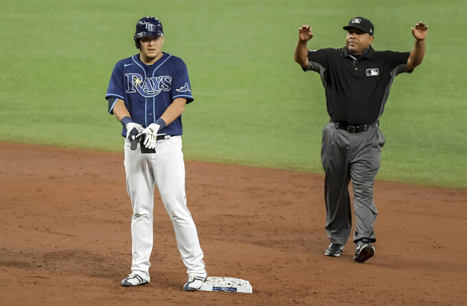 Umpire Adrian Johnson gestures for time out after Tampa Bay Rays' Yoshi Tsutsugo reaches send base with a double off Oakland Athletics' Frankie Montas during the second inning of a baseball game Tuesday, April 27, 2021, in St. Petersburg, Fla. (AP Photo/Steve Nesius)
