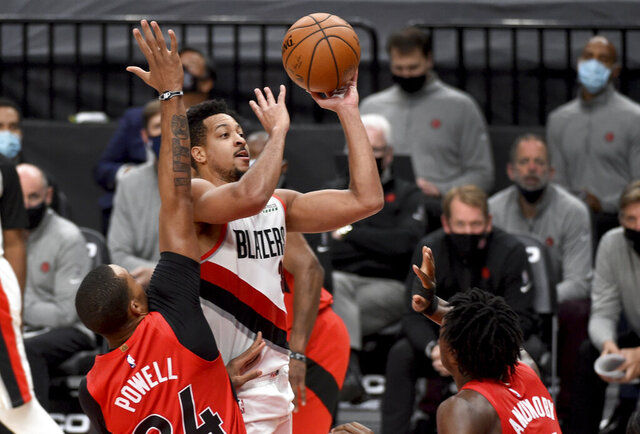 Portland Trail Blazers guard CJ McCollum, center, drives to the basket on Toronto Raptors guard Norman Powell, left, and forward OG Anunoby, right, during the second half of an NBA basketball game in Portland, Ore., Monday, Jan. 11, 2021. The Blazers won 112-111. (AP Photo/Steve Dykes)