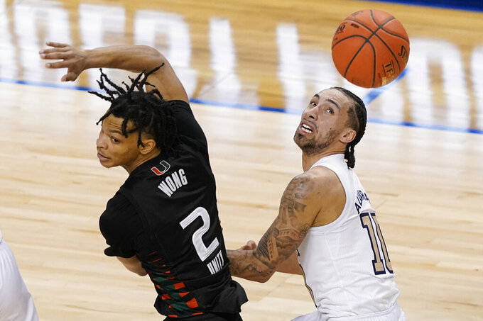 Miami guard Isaiah Wong (2) and Georgia Tech guard Jose Alvarado (10) battle for a loose ball during the second half of an NCAA college basketball game in the quarterfinal round of the Atlantic Coast Conference tournament in Greensboro, N.C., Thursday, March 11, 2021. (AP Photo/Gerry Broome)