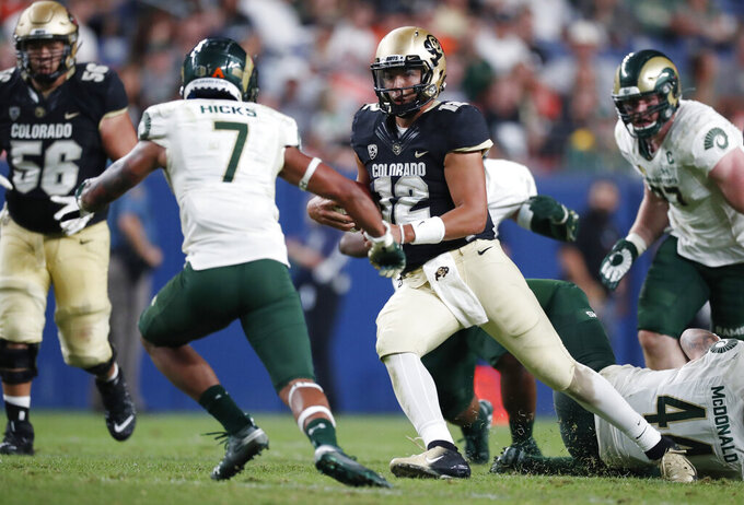 Colorado State safety Jamal Hicks, left, comes in to tackle Colorado quarterback Steven Montez, who ran for a short gain during the third quarter of an NCAA college football game Friday, Aug. 30, 2019, in Denver. (AP Photo/David Zalubowski)