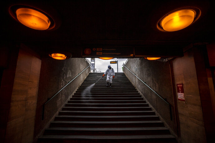 A municipal worker disinfects the subway stairs to prevent the spread of the coronavirus pandemic in Budapest, Hungary, Wednesday, March 25, 2020. The new coronavirus causes mild or moderate symptoms for most people, but for some, especially older adults and people with existing health problems, it can cause more severe illness or death. (Marton Monus/MTI via AP)