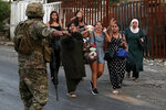 People carry their belongings as they flee their houses after heavy clashes in the coastal town of Khaldeh, south of Beirut, Lebanon, Sunday, Aug. 1, 2021. At least two people were killed on Sunday south of the Lebanese capital when gunmen opened fire at the funeral of a Hezbollah commander who was killed a day earlier, an official from the group said. (AP Photo/Bilal Hussein)