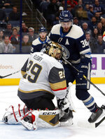 Vegas Golden Knights goalie Marc-Andre Fleury, left, stops a shot in front of Columbus Blue Jackets forward Boone Jenner during the second period of an NHL hockey game in Columbus, Ohio, Tuesday, Nov. 5, 2019. (AP Photo/Paul Vernon)