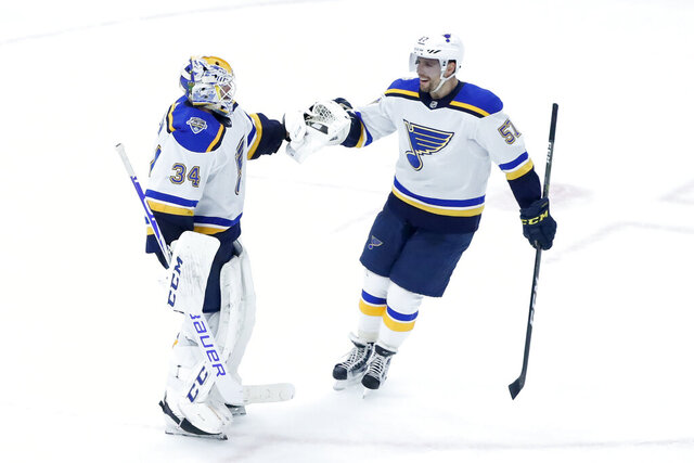 St. Louis Blues goaltender Jake Allen, left, and David Perron celebrate their win over the Chicago Blackhawks in an NHL hockey game Monday, Dec. 2, 2019, in Chicago. (AP Photo/Charles Rex Arbogast)