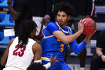UCLA guard Johnny Juzang (3) protects the ball from Alabama guard John Petty Jr. (23) in the first half of a Sweet 16 game in the NCAA men's college basketball tournament at Hinkle Fieldhouse in Indianapolis, Sunday, March 28, 2021. (AP Photo/Michael Conroy)