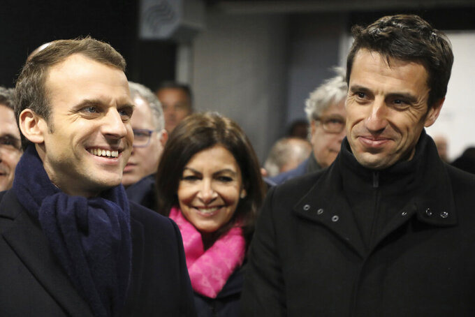 FILE - In this Feb. 27, 2018, file photo, France's President Emmanuel Macron, Paris mayor Anne Hidalgo, center, and Paris 2024 Games' chief Tony Estanguet, right, attend the inauguration of the Olympic Committee site for the Paris 2024 Olympic games and 2024 Paralympic games at the Stade de France stadium in Saint-Denis, outside Paris. The 2024 Paris Olympics emerges fully on Sunday, Aug. 8, 2021, from its unexpected extra year in the shadows with a formal handover from Tokyo. Macron and Estanguet began working together within days of the French presidential election in May 2017. (Ludovic Marin/Pool Photo via AP, File)