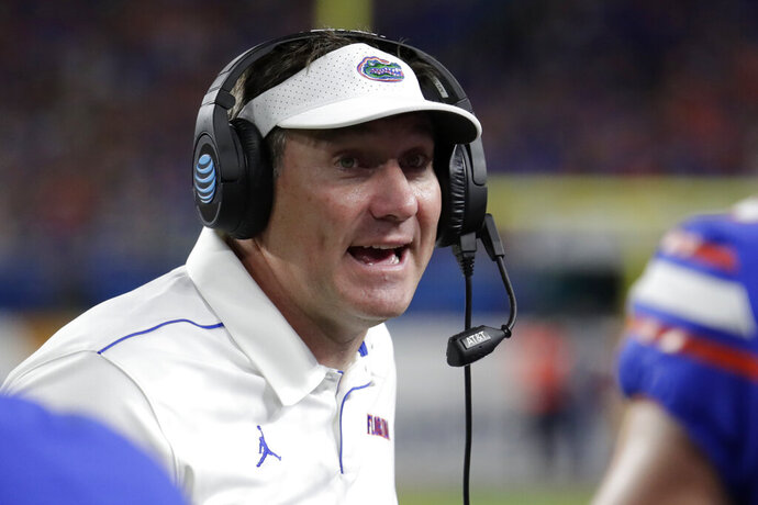 FILE - In this Dec. 30, 2019, file photo, Florida head coach Dan Mullen watches the second half of the Orange Bowl NCAA college football game against Virginia in Miami Gardens, Fla. No. 10 Florida resumed meetings and practices for the first time in two weeks Monday, Oct. 26, 2020. They got back to work after a COVID-19 outbreak caused the Southeastern Conference to postpone two of the team's games. (AP Photo/Lynne Sladky, File)