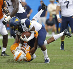 West Virginia's Leddie Brown (4) is tackled by Tennessee's Nigel Warrior (18) in the second half of an NCAA college football game in Charlotte, N.C., Saturday, Sept. 1, 2018. (AP Photo/Chuck Burton)