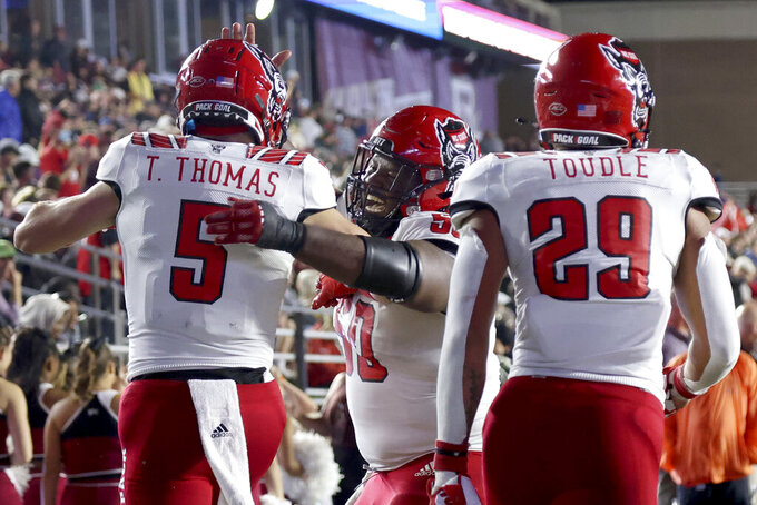 North Carolina State center Grant Gibson (50) congratulates Thayer Thomas (5) after Thomas scored a touchdown during the second half of an NCAA college football game against Boston College, Saturday, Oct. 16, 2021, in Boston. (AP Photo/Mary Schwalm)