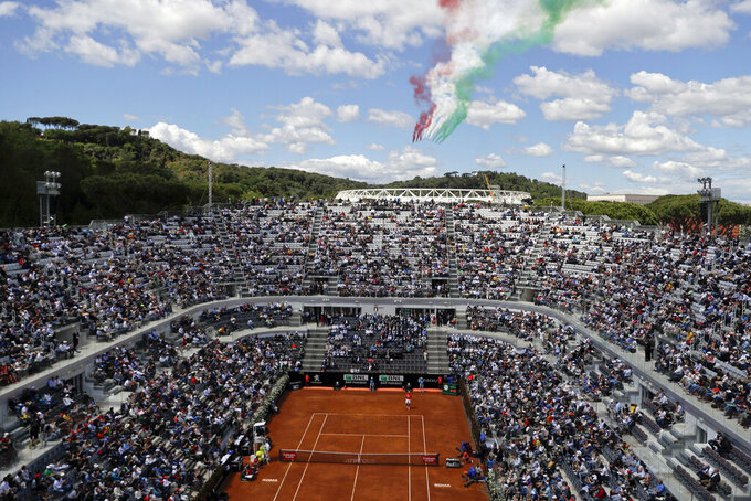 FILE - In this Thursday, May, 16, 2019 file photo, the Italian Air Force aerobatic team Frecce Tricolori (Three-Color Arrows) flies over the central court stadium during the Italian Open tennis tournament, in Rome. The Italian Open men's tournament next month could be expanded from 64 to 96 players and have three more days of matches as tennis officials scramble to rewrite their schedule amid the coronavirus pandemic. The ATP Tour approached Rome organizers with an expansion proposal and offered to cover the extra prize money that would be needed, Italian Tennis Federation president Angelo Binaghi said Wednesday, Aug. 5, 2020. (AP Photo/Gregorio Borgia, File)