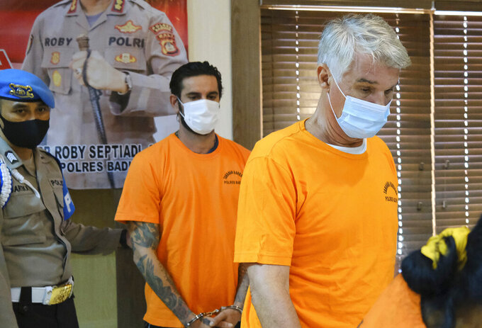 British national Kenneth Daniel Kutsch, right, and Italian national Francesco D'alesio, walk as they are shown to the media during a police press conference in Badung, Bali, Indonesia, Monday, May 24, 2021. The British hotel owner and the Italian tourist were arrested for alleged possession of narcotics on Indonesia's resort island of Bali, police announced Monday. (AP Photo)