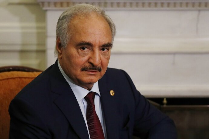 FILE - In this Jan. 17, 2020, file, photo, Libyan Gen. Khalifa Hifter joins a meeting with the Greek Foreign Minister Nikos Dendias in Athens. Two families targeted in a campaign of violence more than five years ago are suing Khalifa Hifter, the military leader of east Libya in a suburban Virginia court. Hifter, a United States citizen and former Virginia resident, is accused of carrying out extrajudicial killings and torture under a rarely invoked law that allows for victims of these crimes committed in other countries to sue foreign officials in U.S. courts. (AP Photo/Thanassis Stavrakis, File)