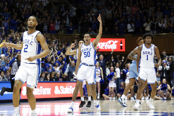 Duke forward Justin Robinson (50) reacts following a basket against North Carolina with guard Cassius Stanley (2) and center Vernon Carey Jr. (1) during the second half of an NCAA college basketball game in Durham, N.C., Saturday, March 7, 2020. (AP Photo/Gerry Broome)