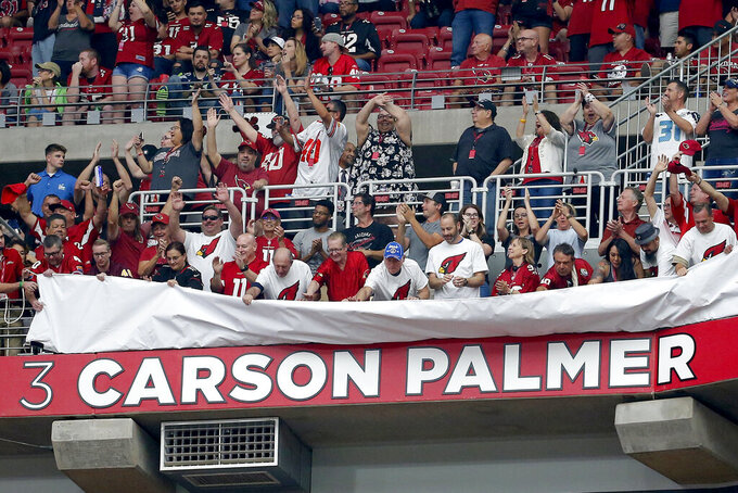 Fans unveil former Arizona Cardinals quarterback Carson Palmer's name in the Cardinals' ring of honor at half time an NFL football game against the Seattle Seahawks, Sunday, Sept. 29, 2019, in Glendale, Ariz. (AP Photo/Rick Scuteri)