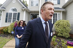 Actor Alec Baldwin, right ,walks with Amanda Pohl, candidate for Virginia Senate District 11, as they leave a home in her neighborhood in Midlothian, Va., Tuesday, Oct. 22, 2019. Baldwin campaigned for several candidates around the state. (AP Photo/Steve Helber)