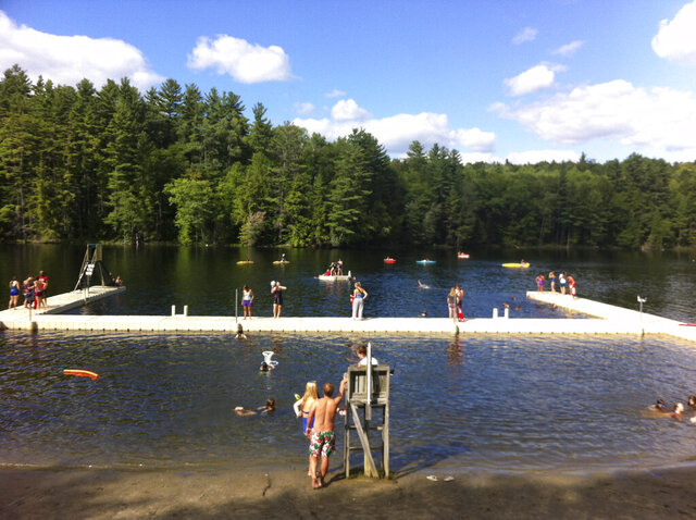 This image released by Forest Lake Camp shows swimmers and kayakers on the lake at the camp in Warrensburg, N.Y. Summer camps have begun to notify families that they won't open due to the coronavirus crisis. Most, however, are in wait-and-see mode as parents who rely on camp for child care as well as child fun try not to panic. (Forest Lake Camp via AP)