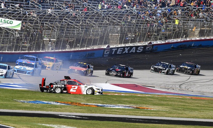 Brad Keselowski (2) wrecks into the grass on the front stretch during a NASCAR auto race at Texas Motor Speedway, Sunday, Nov. 3, 2019, in Fort Worth, Texas. (AP Photo/Larry Papke)
