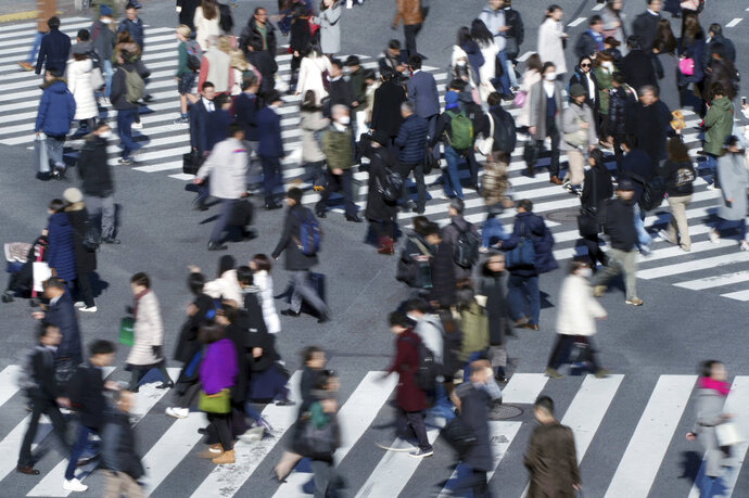 In this Jan. 11, 2018 photo, people walk on a pedestrian crossing at Shibuya district in Tokyo. Japan's economy grew at a slower than expected 0.5 percent annual pace in the October-December quarter, as strong exports failed to fully compensate for relatively weak domestic demand, according to the preliminary data released Wednesday, Feb. 14, 2018. (AP Photo/Eugene Hoshiko)