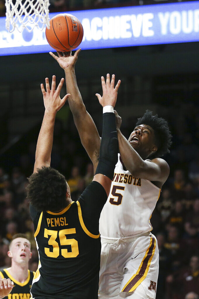 Minnesota's Marcus Carr, right, shoots against Iowa's Cordell Pemsl during an NCAA college basketball game Sunday, Feb. 16, 2020, in Minneapolis. (AP Photo/Stacy Bengs)