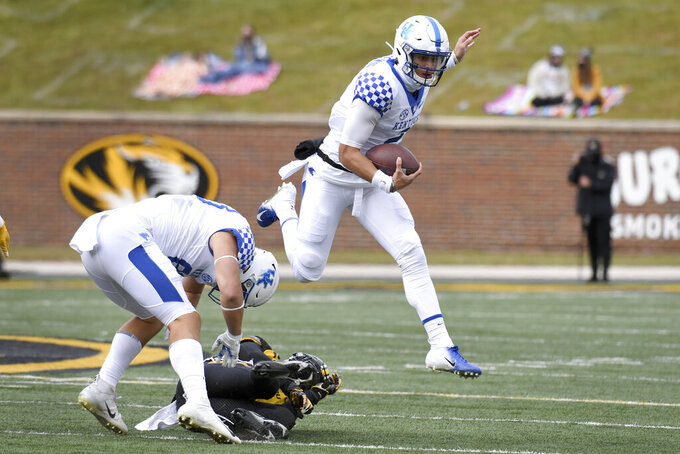 Kentucky quarterback Joey Gatewood, right, leaps in the air as he scrambles during the first half of an NCAA college football game Saturday, Oct. 24, 2020, in Columbia, Mo. (AP Photo/L.G. Patterson)