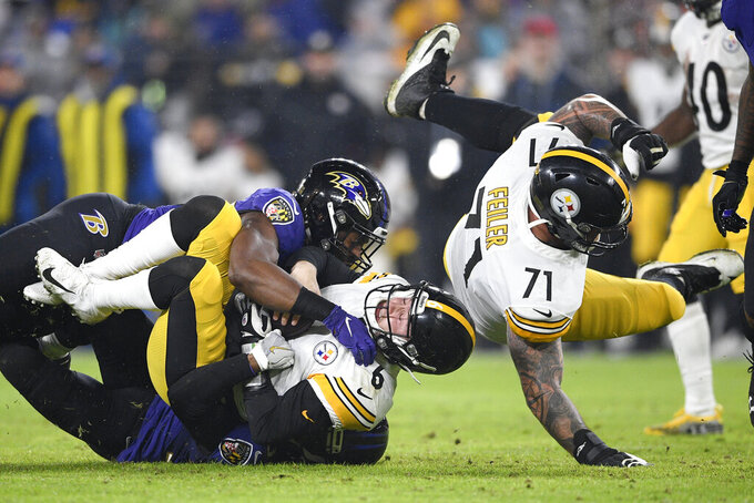 Pittsburgh Steelers quarterback Devlin Hodges (6) is sacked by Baltimore Ravens cornerback Brandon Carr, bottom and outside linebacker Matt Judon, top, during the first half of an NFL football game, Sunday, Dec. 29, 2019, in Baltimore. Steelers' offensive tackle Matt Feiler (71) falls on the play. (AP Photo/Nick Wass)