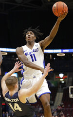 Buffalo's Jeenathan Williams (11) drives to the basket against Akron's Scott Walter (14) during the second half of an NCAA college basketball game of the Mid-American Conference tournament, Thursday, March 14, 2019, in Cleveland. Buffalo won 82-46. (AP Photo/Tony Dejak)