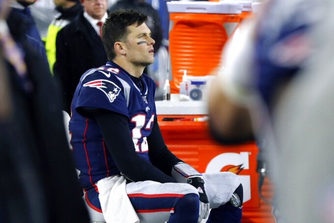 New England Patriots quarterback Tom Brady sits on the bench after throwing an interception that Tennessee Titans cornerback Logan Ryan returned for a touchdown late in the second half of an NFL wild-card playoff football game, Saturday, Jan. 4, 2020, in Foxborough, Mass. (AP Photo/Bill Sikes)