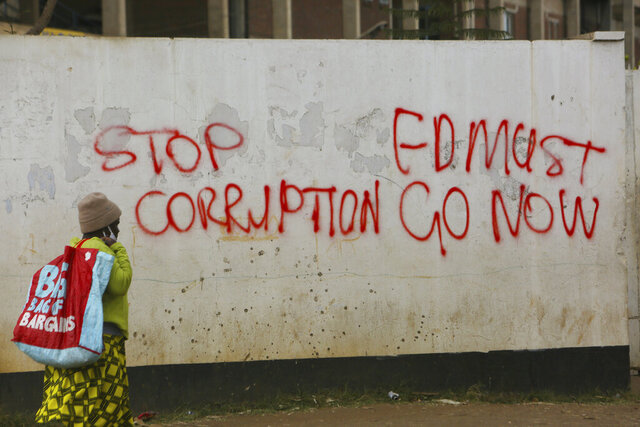 A woman walks past a wall with graffiti calling on the government to stop corruption in this Monday, June, 15, 2020 photo. Unable to protest on the streets, some in Zimbabwe are calling themselves
