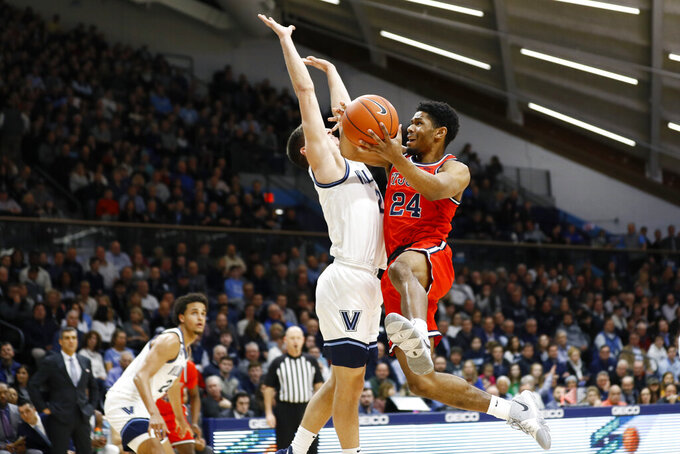 St. John's Nick Rutherford (24) goes up for a shot against Villanova's Collin Gillespie (2) during the first half of an NCAA college basketball game, Wednesday, Feb. 26, 2020, in Villanova, Pa. (AP Photo/Matt Slocum)