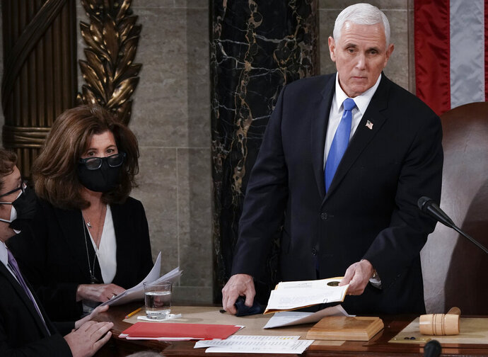 In this Jan. 6, 2021, photo, Senate Parliamentarian Elizabeth MacDonough, second from left, works beside Vice President Mike Pence during the certification of Electoral College ballots in the presidential election, in the House chamber at the Capitol in Washington. Shortly afterward, the Capitol was stormed by rioters determined to disrupt the certification. MacDonough has guided the Senate through two impeachment trials, vexed Democrats and Republicans alike with parliamentary opinions and helped rescue Electoral College certificates from a pro-Trump mob ransacking the Capitol. (AP Photo/J. Scott Applewhite)