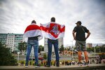 CORRECTING COUNTRY IN CAPTION TO BELARUS - People cover themselves by old Belarusian, centre, and with Belarusian National national flags, a symbol of opposition, as they gather in a street protesting the election results in Minsk, Belarus, Wednesday, Aug. 12, 2020. The demonstrators are contesting the official count showing President Alexander Lukashenko winning a sixth term with 80% of Sunday's vote, with crowds taking to the streets every night since to demand a recount. (AP Photo)