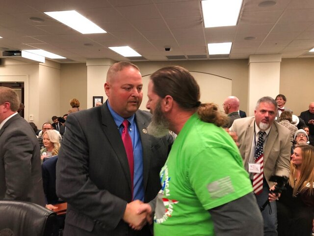 State Rep. John Sims Jr., left,is  congratulated by a medical marijuana advocate on Wednesday, Feb. 12, 2020, in Frankfort, Ky., after the House Judiciary Committee advanced a bill to legalize medical cannabis in Kentucky. The bill heads to the full House next. (AP Photo/Bruce Schreiner)