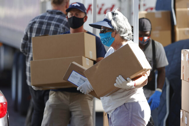 FILE - In this June 26, 2020, file photo, volunteers Juanita MacKenzie, front, and Dave Stutman carry boxes of food to a waiting car at a large mobile pantry set up by the Food Bank of the Rockies in the parking lot of Empower Field at Mile High in west Denver. In an effort to keep Colorado residents fed and employed this winter, Colorado's Legislature is concluding a special session Wednesday, Dec. 2, 2020, by passing bills offering assistance to restaurants and food pantries struggling to keep their doors open during the coronavirus pandemic. (AP Photo/David Zalubowski, File)