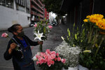 Lucia Nieto assembles an arrangement of flowers for a customer, as she, her husband, and daughter sell fresh flowers from their family cart, in central Mexico City, Sunday, May 31, 2020. Mexico's capital plans to reopen certain sectors of the economy and public life beginning Monday, despite the city still being in the most serious