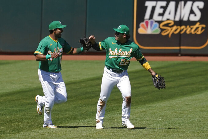Oakland Athletics shortstop Elvis Andrus, left, celebrates with center fielder Ramon Laureano after the Athletics defeated the Seattle Mariners in a baseball game in Oakland, Calif., Wednesday, May 26, 2021. (AP Photo/Jeff Chiu)