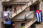 People wait to be vaccinated with the Cuban Abdala vaccine for COVID-19 at a doctors' office, decorated with an image of Fidel Castro and a Cuban flag, in the Alamar neighborhood of Havana, Cuba, Friday, May 14, 2021. Cuba began immunizing people this week with its own vaccines, Abdala and Soberana 02, the only ones developed by a Latin American country. (AP Photo/Ramon Espinosa)