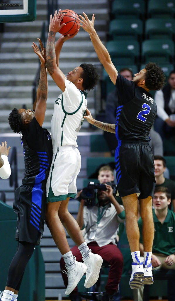 Eastern Michigan forward Elijah Minnie shoots between Buffalo forward Montell McRae, left, and guard Jeremy Harris (2) during the first half of an NCAA college basketball game Friday, Jan. 4, 2019, in Ypsilanti, Mich. (AP Photo/Duane Burleson)
