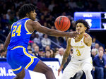Notre Dame's Prentiss Hubb (3) passes around UCLA's Jalen Hill (24) during the first half of an NCAA college basketball game Saturday, Dec. 14, 2019, in South Bend, Ind. (AP Photo/Robert Franklin)
