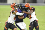Baltimore Ravens running back Mark Ingram, center, is hit by Cincinnati Bengals free safety Jessie Bates, left, and cornerback William Jackson during the second half of an NFL football game, Sunday, Oct. 11, 2020, in Baltimore. (AP Photo/Nick Wass)