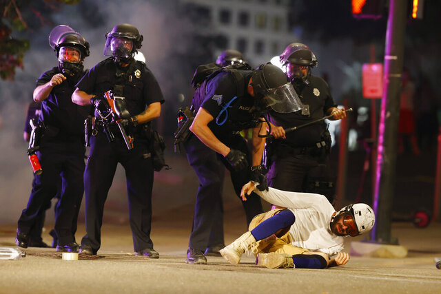 Denver Police Department officers clear a man who fell to the street after they used tear gas and rubber bullets to disperse a protest outside the State Capitol over the death of George Floyd, a handcuffed black man who died in police custody in Minneapolis, late Thursday, May 28, 2020, in Denver. (AP Photo/David Zalubowski)