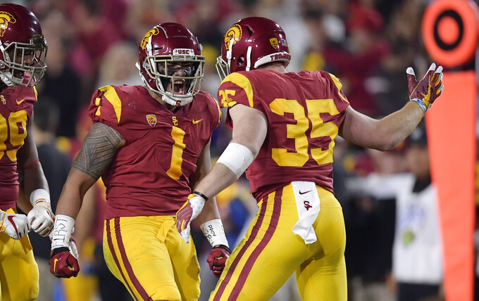 Southern California linebacker Palaie Gaoteote IV, center, celebrates a sack with defensive lineman Christian Rector, left, and linebacker Cameron Smith during the first half of an NCAA college football game against Notre Dame on Saturday, Nov. 24, 2018, in Los Angeles. (AP Photo/Mark J. Terrill)
