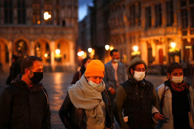 Passers-by, wearing face masks to prevent the spread of coronavirus, walk along the Grande Place or Grand Square in downtown Brussels, Wednesday, Oct. 14, 2020. The latest COVID-19 figures published Wednesday by the national institute of public health show that a total of  over 7,000 extra coronavirus cases have been recorded in 24 hours in Belgium. (AP Photo/Francisco Seco)