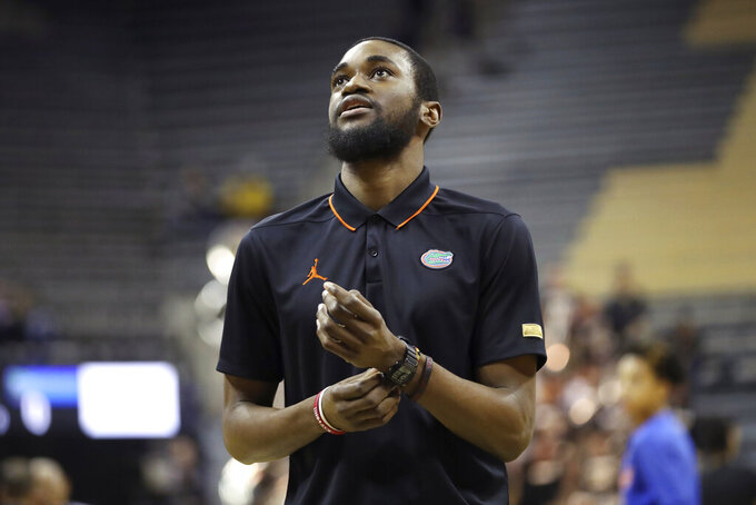 In this Jan. 11, 2020, photo provided by the University of Florida Athletic Association, Florida team manager Chris Sutherland is shown during an NCAA college basketball game against Missouri in Columbia, Mo. Sutherland waited nearly five years to finally play college basketball. He worked his way onto Florida's bench in January after serving as an arena worker, a practice player for the women's team and a team manager for the men's program. Gaining NCAA eligibility was a daunting task that required him to repay a $5,000 scholarship and remove his name and likeness off a website he created last year to sell streetwear he designed. (Alex de la Osa/UAA Communications via AP)