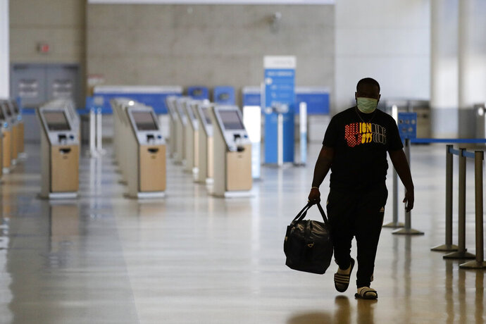 A traveler walks in a mostly empty American Airlines terminal at the Los Angeles International Airport, Thursday, May 28, 2020, in Los Angeles. From Britain's EasyJet to American and Delta in the U.S., airlines are cutting even more jobs to cope with a crushing drop in air travel caused by the coronavirus pandemic. (AP Photo/Marcio Jose Sanchez)
