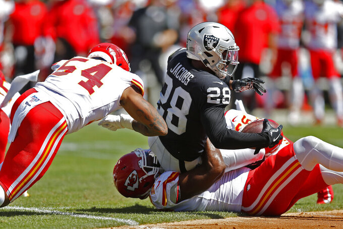 Oakland Raiders running back Josh Jacobs (28) is stopped with the ball by Kansas City Chiefs defensive end Alex Okafor, below, and outside linebacker Damien Wilson (54) during the first half of an NFL football game Sunday, Sept. 15, 2019, in Oakland, Calif. (AP Photo/D. Ross Cameron)
