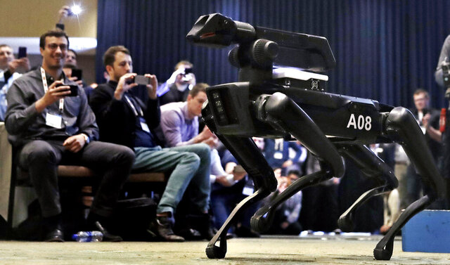FILE - In this May 24, 2018, file photo, a Boston Dynamics SpotMini robot walks through a conference room during a robotics summit in Boston. Boston Dynamics on Tuesday, June 16, 2020 started selling its four-legged Spot robots online for just under $75,000 each. The agile robots can walk, climb stairs and open doors. But people who buy them online must agree not to arm them or intentionally use them as weapons, among other conditions. (AP Photo/Charles Krupa, File)