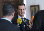 FILE - In this March 4, 2018 file photo provided by the official Facebook page of the Syrian Presidency, Syrian President Bashar Assad, center, speaks with reporters, in Damascus, Syria. In comments published on the official presidency Telegram channel Wednesday, March 14, 2018, Assad said his country's war on terrorism will continue as long as there is