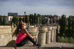 A woman enjoys the sun at the Toledo bridge in Madrid, Spain, Sunday, May 3, 2020. On Saturday, Spaniards were able to go outdoors to do exercise for the first time in seven weeks since the lockdown began to battle the coronavirus outbreak. (AP Photo/Manu Fernandez)